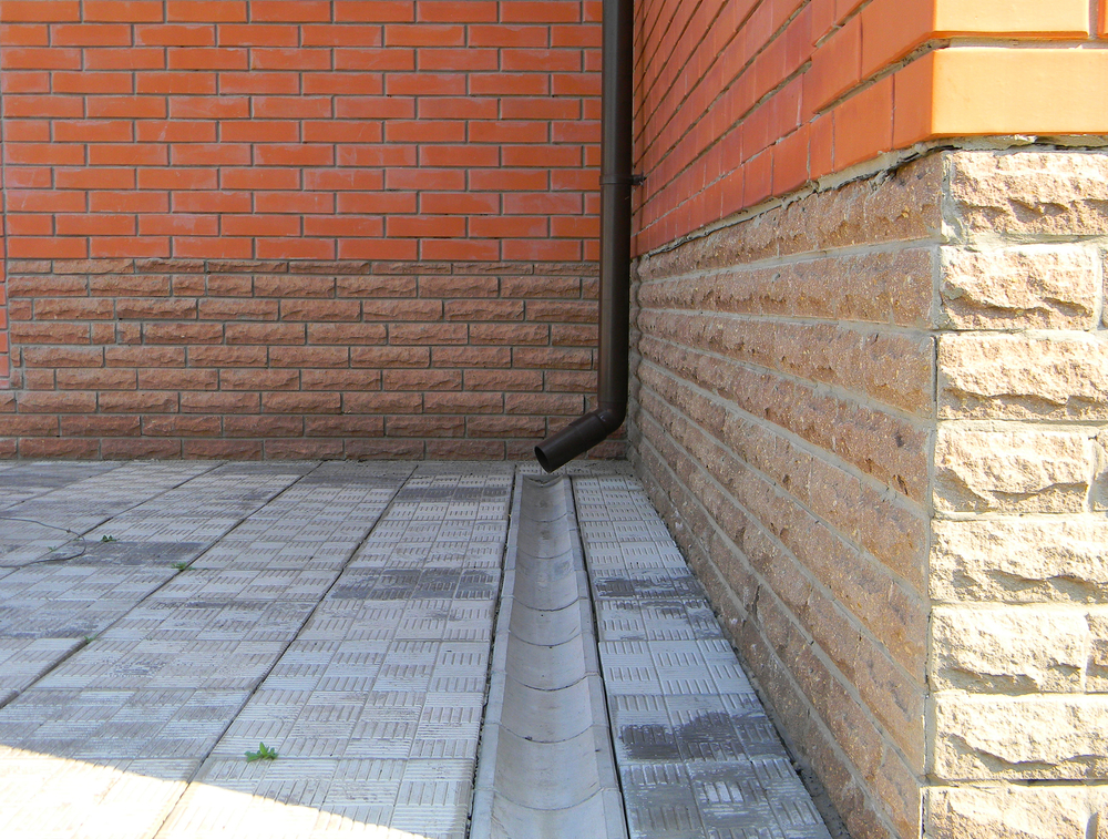 Closeup of rain gutter and drainage system on the footpath